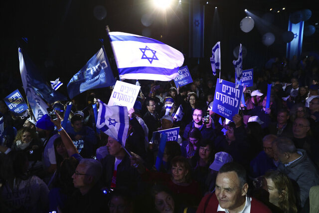 Blue and White party supporters hold banners and flags during an election campaign rally in Tel Aviv, Israel, Saturday, Feb. 29, 2020. The Hebrew writing say