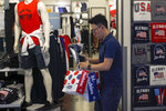 FILE - In this July 15, 2019, file photo, a man buys clothes from an American clothing store having a promotion sale at a shopping mall in Beijing. Companies who do business with China walk a fine line to stay aligned with U.S. values such as freedom of speech and democracy while avoiding offending China, where they stand to make billions of dollars. (AP Photo/Andy Wong, File)