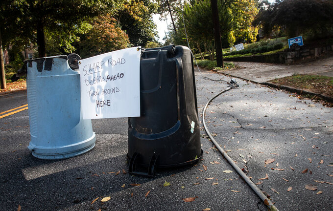 Handwritten warning signs are taped to garbage cans on a street blocked by a tree downed after the passage of Hurricane Zeta, Thursday, Oct. 29, 2020, in Decatur, Ga., a suburb of Atlanta. Trees in several areas in and around Atlanta lay broken or resting on sagging power and communication lines, some of which snapped telephone poles. (AP Photo/Ron Harris)