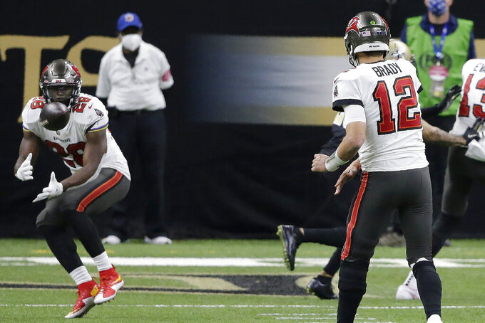 Tampa Bay Buccaneers quarterback Tom Brady (12) throws the ball to running back Leonard Fournette (28) for a touchdown against the New Orleans Saints during the second half of an NFL divisional round playoff football game, Sunday, Jan. 17, 2021, in New Orleans. (AP Photo/Butch Dill)