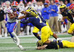 Florida running back Jordan Scarlett (25) runs by Michigan linebacker Khaleke Hudson (7) during the first half of the Peach Bowl NCAA college football game, Saturday, Dec. 29, 2018, in Atlanta. (AP Photo/John Bazemore)