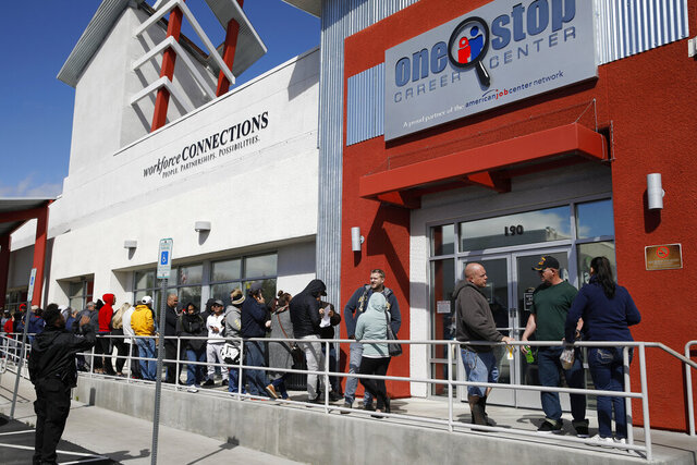 FILE - In this March 17, 2020, file photo, people wait in line for help with unemployment benefits at the One-Stop Career Center in Las Vegas. The coronavirus pandemic has been particularly brutal to the tourism-dependent economies of Nevada and Hawaii, lifting the unemployment rate in both states to about one-quarter of the workforce. (AP Photo/John Locher, File)