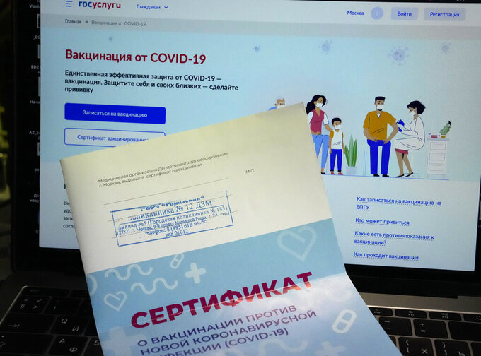 A vaccination certificate sits on a computer screen with the website Gosuslugi (public services portal) in Moscow, Russia, Monday, June 21, 2021. Police quickly cracked down, launching 24 criminal cases last week against sellers of fake vaccination certificates. Still, several accounts offering the bogus documents could be found easily on the Telegram messaging app this week. (AP Photo/Alexander Zemlianichenko)