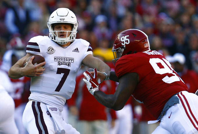 Mississippi State quarterback Nick Fitzgerald (7) is pressured by Alabama defensive lineman Johnny Dwight (95) during the first half of an NCAA college football game, Saturday, Nov. 10, 2018, in Tuscaloosa, Ala. (AP Photo/Butch Dill)