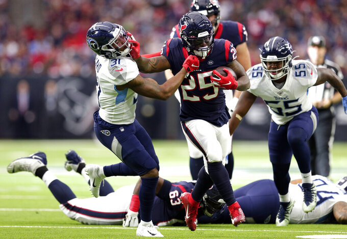 Houston Texans running back Duke Johnson (25) rushes for a gain as Tennessee Titans free safety Kevin Byard (31) reaches to tackle him during the first half of an NFL football game Sunday, Dec. 29, 2019, in Houston. (AP Photo/Michael Wyke)