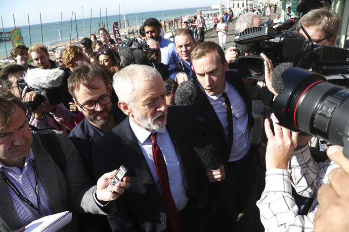Labour Party leader Jeremy Corbyn, walking along the promenade, is met by the press on the way to the Labour Party Conference at the Brighton Centre in Brighton, England. Saturday Sept. 21, 2019. (Gareth Fuller/PA via AP)
