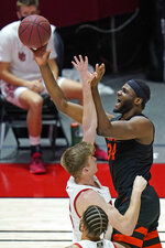 Oregon State forward Rodrigue Andela (34) shoots as Utah center Branden Carlson, left, defends during the first half of an NCAA college basketball game Wednesday, March 3, 2021, in Salt Lake City. (AP Photo/Rick Bowmer)