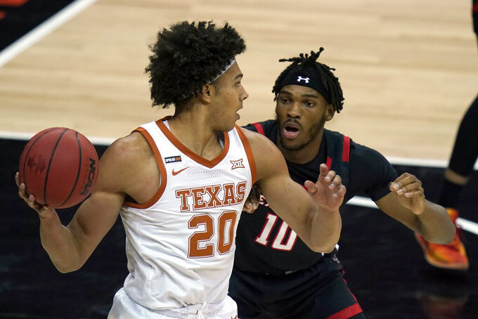 Texas forward Jericho Sims (20) looks to pass while covered by Texas Tech Red forward Tyreek Smith (10) during the first half of an NCAA college basketball game in the quarterfinal round of the Big 12 men's tournament in Kansas City, Mo., Thursday, March 11, 2021. (AP Photo/Orlin Wagner)