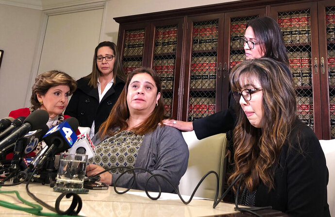 Attorney Gloria Allred, lower left, listens as one of four Park Avenue Elementary School teachers talks about her experiences when a Delta Airlines jet dumped fuel over their school Tuesday, Jan. 14, 2020, at a Los Angeles news conference Friday, Jan. 17, 2020. The four plaintiffs in a lawsuit against Delta - Lisette Barajas, Laura Guzman, Mariana De La Torre and Anabel Samperio - appeared at the news conference but declined to be identified individually when they spoke. The teachers plan to file a lawsuit after a commercial airliner with engine trouble dumped jet fuel over a densely populated area. (AP Photo/Stefanie Dazio)