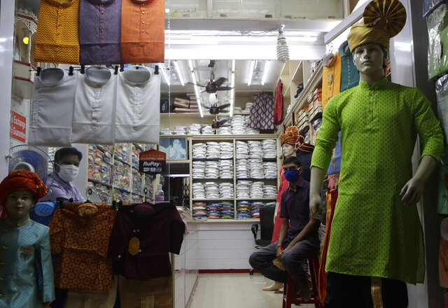 A shopkeeper and his staff wait for customers at a garment store in Mumbai, India, Monday, Aug. 31, 2020. India's economy contracted by 23.9% in the April-June quarter, its worst performance in at least 24 years, the government announced Monday, as the coronavirus pandemic ravaged what was once the world's fastest growing major economy. (AP Photo/Rajanish Kakade)