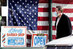 A customer wears a mask as he walks to a barber shop in Libertyville, Ill., Thursday, Dec. 3, 2020. Thousands of Illinois businesses received millions in loans under a federal government program created to help small companies recover from the economic crisis left in the wake of the pandemic. (AP Photo/Nam Y. Huh)