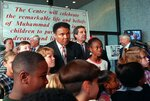 """FILE - Muhammad Ali poses with third-graders following a press conference called to announce the development of The Muhammad Ali Center in Louisville, Ky., in this Wednesday, Oct. 7, 1998, file photo. A new documentary looks at the city that raised Muhammad Ali, Louisville, Kentucky, and the week of his funeral, when the community came together to celebrate the legacy of """"The Greatest."""" (AP Photo/Brian Bohannon, File)"""