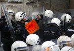Protesters throw a traffic cone towards a police cordon in front of the Belgrade police headquarters in Belgrade, Serbia, Sunday, March 17, 2019. The opposition clashes with police on Saturday and Sunday in Belgrade, the capital, were the first major incidents after months of peaceful protests against populist President Aleksandar Vucic. The demonstrators are demanding his resignation, fair elections and a free media. . (AP Photo/Darko Vojinovic)