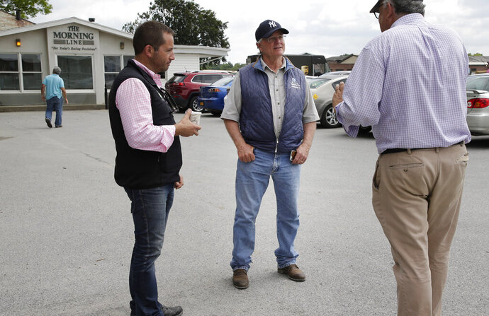 Trainer Bill Mott, second from right, stops to talk to people at Belmont Park in Elmont, N.Y., Thursday, June 6, 2019. The 151st Belmont Stakes horse race will be run on Saturday, June 8, 2019. (AP Photo/Seth Wenig)