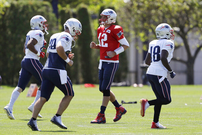 New England Patriots quarterback Tom Brady, center right, smiles while warming up with teammates, from left, tight end Stephen Anderson, long snapper Joe Cardona, and wide receiver Matthew Slater during an NFL football practice, Monday, Aug. 26, 2019, in Foxborough, Mass. (AP Photo/Steven Senne)
