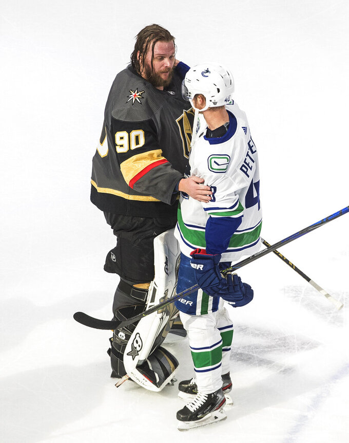 Vancouver Canucks' Elias Pettersson (40) and Vegas Golden Knights goalie Robin Lehner (90) greet one another after Game 7 of an NHL hockey second-round playoff series, Friday, Sept. 4, 2020, in Edmonton, Alberta. (Jason Franson/The Canadian Press via AP)