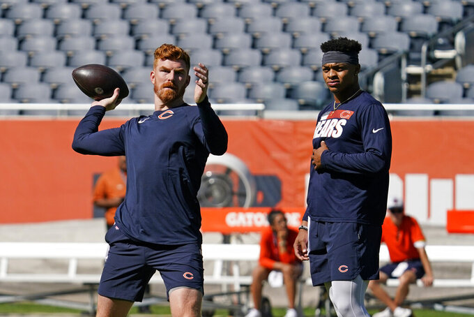 FILE - Chicago Bears quarterback Andy Dalton, left, looks to pass as quarterback Justin Fields watches as they warmup before an NFL preseason football game against the Miami Dolphins in Chicago, in this Saturday, Aug. 14, 2021, file photo. Justin Fields looked like he was ready to play during the preseason. But with veteran Andy Dalton penciled in as the No. 1 quarterback, it remains to be seen when the Chicago Bears' prized rookie will play again. Another question is how short a leash Dalton will be on with the former Ohio State star behind him. (AP Photo/Nam Y. Huh, File)