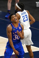 Kansas' Ochai Agbaji (30) reacts after dunking and being fouled by Kentucky's Isaiah Jackson (23) during the second half of an NCAA college basketball game Tuesday, Dec. 1, 2020, in Indianapolis. (AP Photo/Darron Cummings)