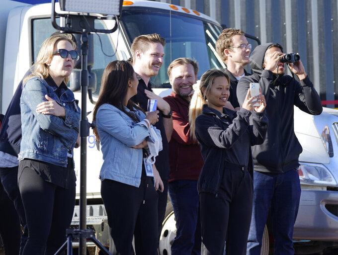 Observers watch Blue Origin's New Shepard rocket launch from its spaceport near Van Horn, Texas, Wednesday, Oct. 13, 2021. (AP Photo/LM Otero)