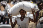 An Ethiopian man carries a sack of wheat on his head to be distributed by the Relief Society of Tigray in the town of Agula, in the Tigray region of northern Ethiopia Saturday, May 8, 2021. A high-level U.N.-led committee that focuses on rapid responses to humanitarian crises estimates that some 350,000 people in Ethiopia's embattled Tigray region are facing famine conditions, a U.N. official said late Wednesday, June 9, 2021. (AP Photo/Ben Curtis)