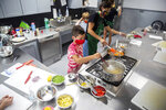 FILE - In this July 21, 2020, file photo, Cole Rossi, 8, keeps an eye on a pot of pasta during a Real Food 4 Kids cooking class taught by Sue Honkamp at Kitchen Spaces in Des Moines. Since August 2019, owner Bob Mulvihill has been renting Kitchen Spaces to entrepreneurs who are looking to start their small businesses without the huge capital investment needed to own or rent, remodel and staff a building.(Kelsey Kremer /The Des Moines Register via AP )