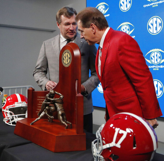 Georgia head coach Kirby Smart, left, speaks with Alabama head coach Nick Saban near near the Championship trophy, Friday, Nov. 30, 2018, in Atlanta. Georgia and Alabama will play Saturday in the Southeastern Conference championship NCAA college football game. (AP Photo/John Bazemore)