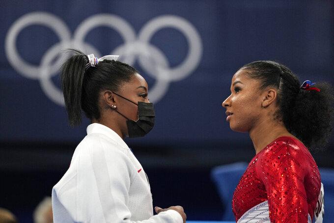 Simone Biles, of the United States, talks to teammate Jordan Chiles prior to the latter's performance on the uneven bars during the artistic gymnastics women's finalat the 2020 Summer Olympics, Tuesday, July 27, 2021, in Tokyo. (AP Photo/Ashley Landis)