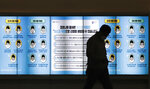 A man wearing a face mask walks past in front of a screen showing precautions against the coronavirus in Seoul, South Korea, Friday, Nov. 20, 2020. The letters read: