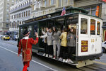 In this photo taken Monday, Jan. 6, 2020, a group of girls riding a Powell Street cable car are greeted by Beefeater doorman Tom Sweeney outside the Sir Francis Drake Hotel in San Francisco. Another bit of old, quirky San Francisco will be no more when Tom Sweeney finally hangs up his white pressed collar and signature Beefeater jacket after more than four decades as chief doorman at downtown's Sir Francis Drake Hotel. Sweeney has opened doors for movie stars and shaken hands with every U.S. president since Gerald Ford, with the exception of Donald Trump. He's taken photos with countless visitors from around the world, often after telling them where to catch the cable car and how to get to Fisherman's Wharf. The man known as a