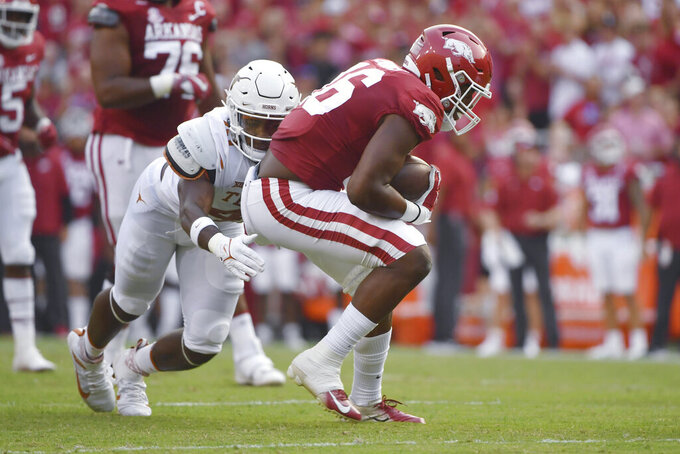 Texas defender Jaylan Ford (41) tackles Arkansas receiver Treylon Burks (16) during the first half of an NCAA college football game Saturday, Sept. 11, 2021, in Fayetteville, Ark. (AP Photo/Michael Woods)