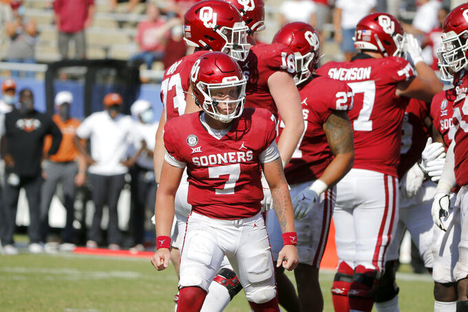 Oklahoma quarterback Spencer Rattler (7) reacts after scoring a touchdown in overtime against Texas during an NCAA college football game in Dallas, Saturday, Oct. 10, 2020. Oklahoma defeated Texas 53-45 in four overtimes. (AP Photo/Michael Ainsworth)