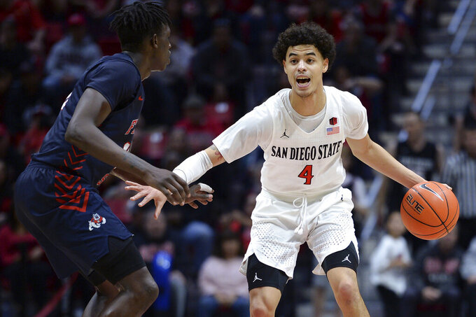 San Diego State guard Trey Pulliam (4) dribbles the ball while defended by Fresno State guard Aguir Agau (13) during the second half of an NCAA college basketball game Wednesday, Jan. 1, 2020, in San Diego. San Diego won 61-52. (AP Photo/Orlando Ramirez)