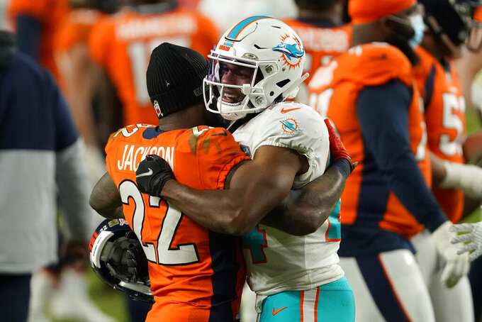 Denver Broncos strong safety Kareem Jackson (22) embraces Miami Dolphins outside linebacker Elandon Roberts after an NFL football game, Sunday, Nov. 22, 2020, in Denver. The Broncos won 20-13. (AP Photo/Jack Dempsey)