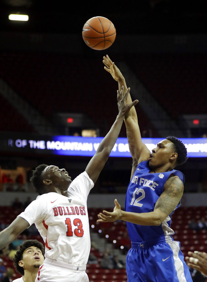 Air Force's Lavelle Scottie (12) shoots as Fresno State's Aguir Agau (13) defends during the first half of an NCAA college basketball game in the Mountain West Conference men's tournament Thursday, March 14, 2019, in Las Vegas. (AP Photo/Isaac Brekken)