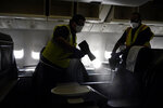 Workers with ABM Industries give a demostration on cleaning inside a United Airlines plane destined for Hawaii at San Francisco International Airport in San Francisco, Thursday, Oct. 15, 2020. Coronavirus weary residents and struggling business owners in Hawaii will be watching closely as tourists begin to return to the islands on Thursday without having to self-quarantine upon arrival. (AP Photo/Jeff Chiu)