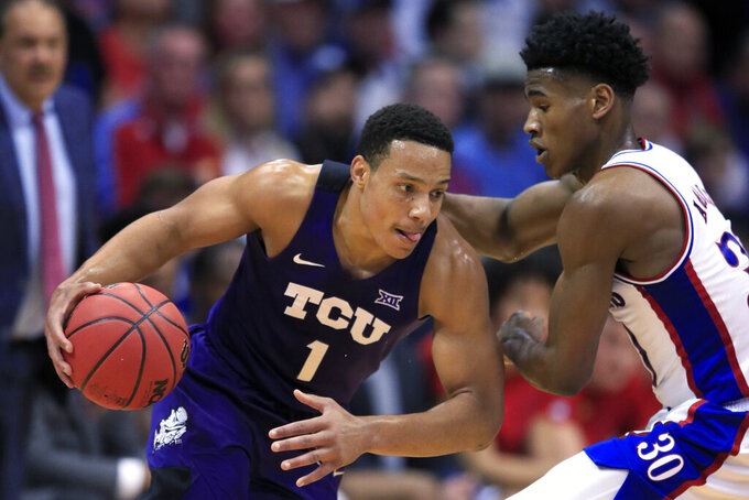 TCU guard Desmond Bane (1) drives on Kansas guard Ochai Agbaji during the first half of an NCAA college basketball game in Lawrence, Kan., Wednesday, March 4, 2020. (AP Photo/Orlin Wagner)