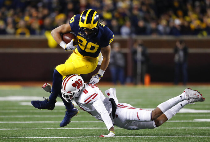 Wisconsin cornerback Deron Harrell (8) tackles Michigan wide receiver Oliver Martin (80) after a reception during the first half of an NCAA college football game in Ann Arbor, Mich., Saturday, Oct. 13, 2018. (AP Photo/Paul Sancya)