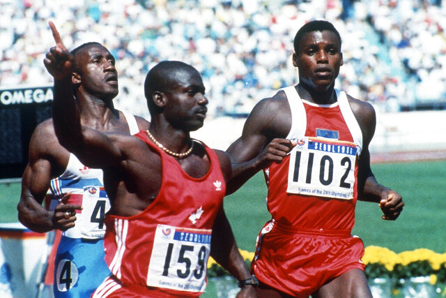 FILE - In this Sept. 25, 1988, file photo, Canadian Ben Johnson, left, signals victory ahead of the United States' Carl Lewis, as he wins the 100-meter final at the Summer Olympic Games in Seoul, South Korea. (AP Photo/Rick Wilking, File)