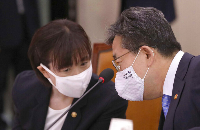 Park Yang-woo, right, minister of the Ministry of Culture, Sports and Tourism, talks with Choi Yoon-hee, left, vice minister of the Ministry of Culture, Sports and Tourism during a parliamentary committee meeting at the National Assembly in Seoul, South Korea, Monday, July 6, 2020. Top South Korean officials on Monday offered a public apology and vowed to delve into the death of a triathlete who had reported to government and sports bodies that she had been abused her team coach, physical therapist and colleagues. (Kim Sun-woong/Newsis via AP)