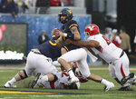 West Virginia quarterback Will Grier (7) is sacked by Youngstown State defensive tackle Wesley Thompson Wesley during the first half of an NCAA college football game Saturday, Sept. 8, 2018, in Morgantown, W.Va. (AP Photo/Raymond Thompson)