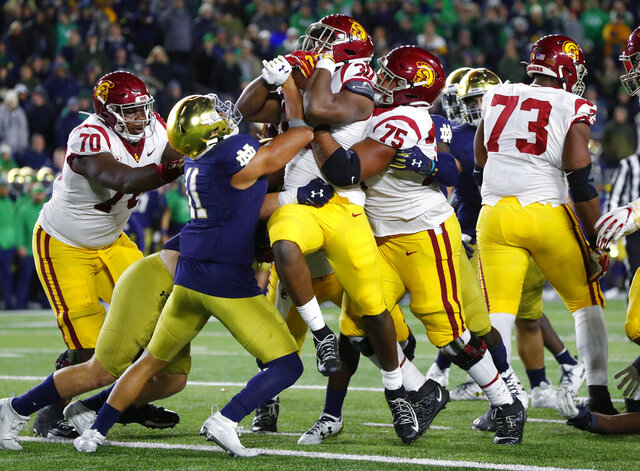 FILE - In this Oct. 12, 2019, file photo, Southern California running back Markese Stepp (30) is lifted into the end zone by Alijah Vera-Tucker (75) as Notre Dame safety Alohi Gilman defends during an NCAA college football game in South Bend, Ind. Vera-Tucker has opted back in to the upcoming season, giving an enormous boost to the Trojans' offense. Vera-Tucker announced his decision Tuesday, Oct. 6, 2020, on social media. He opted out in September when the Pac-12 was uncertain about the resumption of its season. (AP Photo/Paul Sancya, File)