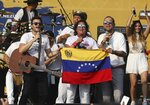 Gusi, from left, Carlos Vives and Santiago Cruz, hold a Venezuelan national flag as they perform at the