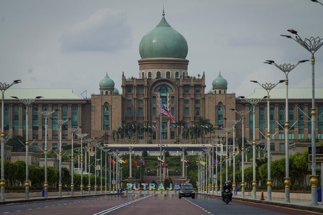 Motorists drive in front of the prime minister's office building in Putrajaya, Malaysia, Friday, Oct. 23, 2020. Malaysian opposition leader Anwar Ibrahim said Friday he was concerned about reports that Prime Minister Muhyiddin Yassi may invoke emergency laws to suspend Parliament and stymie bids to oust his government. (AP Photo/Vincent Thian)