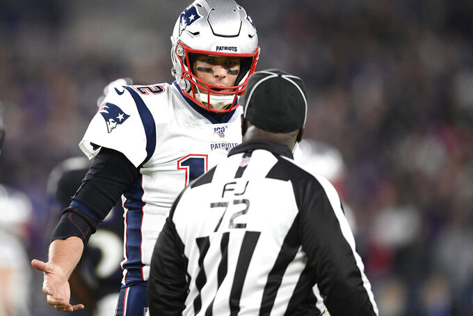 FILE - In this Nov. 3, 2019, file photo, New England Patriots quarterback Tom Brady, left, talks with field judge Michael Banks (72) during the first half of an NFL football game against the Baltimore Ravens, Sunday, in Baltimore. The NFL's 100th season has not been worth celebrating even if the history of the league is.(AP Photo/Nick Wass, File)