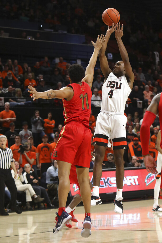 Oregon State's Alfred Hollins (4) takes a shot despite defense from Arizona's Ira Lee (11) during the first half of an NCAA college basketball game in Corvallis, Ore., Thursday, Feb. 28, 2019. (AP Photo/Amanda Loman)