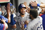 Texas Rangers' Jason Martin is congratulated by teammates after his two-run home run during the sixth inning of the team's baseball game against the Cleveland Indians, Wednesday, Aug. 25, 2021, in Cleveland. (AP Photo/Tony Dejak)