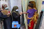 A health worker marks the finger of a child after administrating a polio vaccine in a neighborhood of Lahore, Pakistan, Monday, Aug. 2, 2021. The government launched polio vaccination drives across Pakistan in hopes to eradicate the crippling disease by the end of the year. (AP Photo/K.M. Chaudhry)
