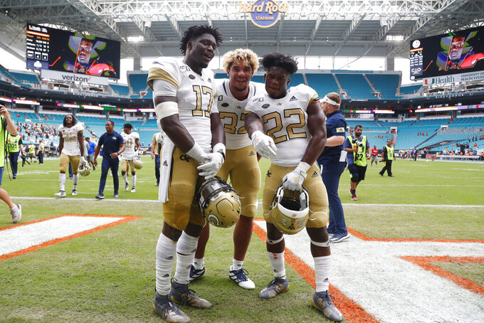 Georgia Tech linebacker Demetrius Knight II (17) defensive lineman Sylvain Yondjouen (32) and running back Jamious Griffin (22) pose as they celebrate after an NCAA college football game against Miami, Saturday, Oct. 19, 2019, in Miami Gardens, Fla. Georgia Tech defeated Miami 28-21 in overtime. (AP Photo/Wilfredo Lee)