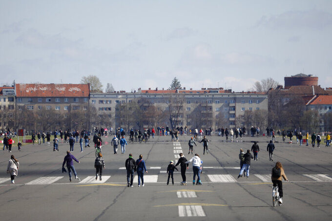 People walk on the runway of the former Tempelhof airport that is now a public park in Berlin, Germany, Friday, April 2, 2021. Due to the coronavirus pandemic only a limited number persons can meet together. (AP Photo/Markus Schreiber)