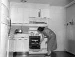 FILE - In this Oct. 10, 1954, file photo, Mrs. John Stamy Jr., checks on dinner cooking in the oven of the electric stove in the kitchen of the Stamy farm, near Newville, Pa. Mrs. Stamy and her husband have electrified their farm to make it attractive to their four young sons as they grow up. Dozens of electrical appliances make work easy in the kitchen. Throughout the house more than 54 circuits handle current for all sorts of appliances, Electrical outlets are placed so that at no point is one more than six feet away, for convenient use. The California Energy Commission released a draft building standards code on Thursday, May 6, 2021, that would require new homes to be equipped with circuits and panels that support all-electric appliances for heating, cooking and drying clothes. (AP Photo, File)